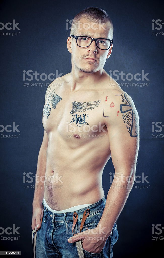 Tattooed young man posing against grunge background royalty-free stock photo