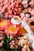VORONEZH/RUSSIA-05.03.2018: Tattooed young man's hand holding fresh espresso coffee cup on the beautiful blossoming fresh flower bed background of coral peonies, roses, pink carnations, tulips.