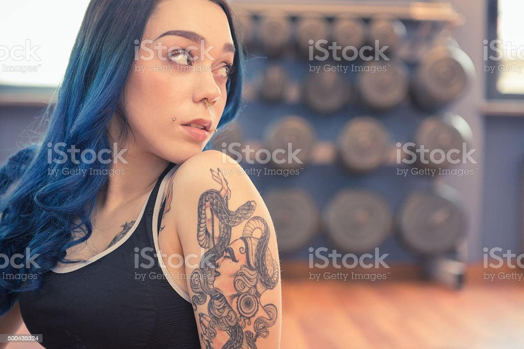 tattooed young womanwith blue hair exercising in gym pole dance tattooed young woman with bleu hair exercising in gym pole dance: really nice suicide girl. 20-29 Years Stock Photo