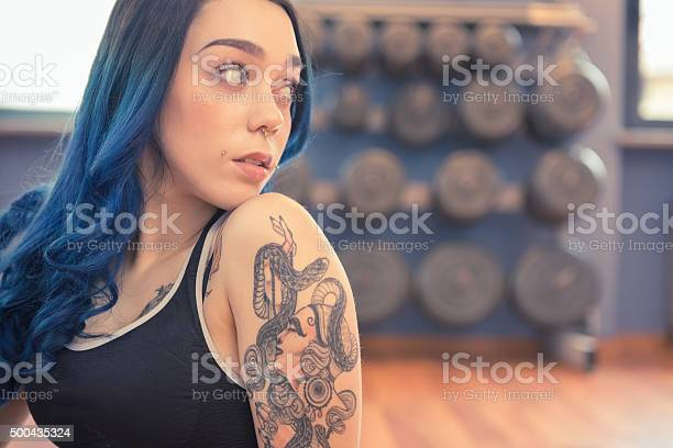 Tattooed Young Womanwith Blue Hair Exercising In Gym Pole Dance Stock Photo - Download Image Now