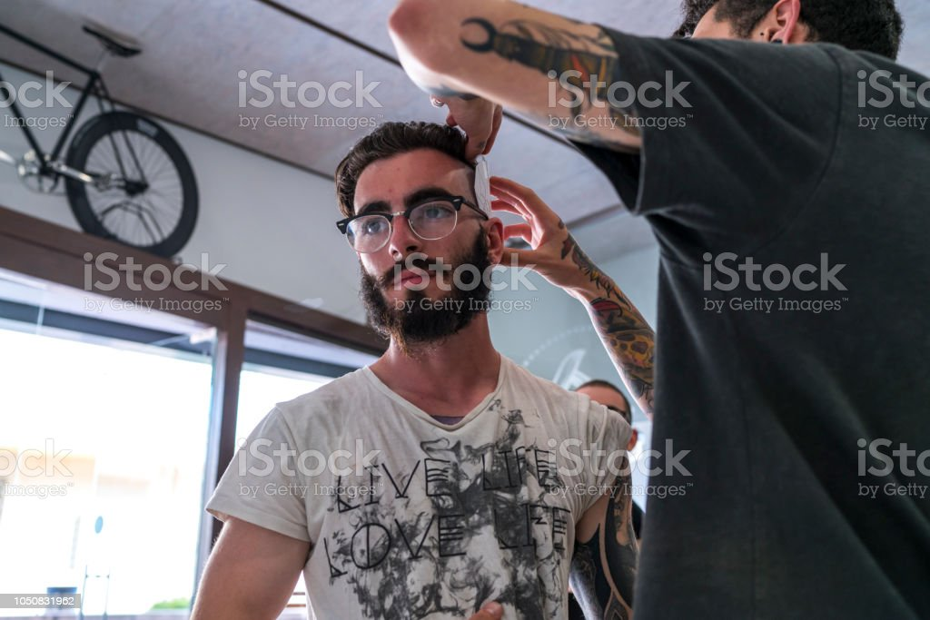 Tattooist placing the drawing on the head стоковое фото