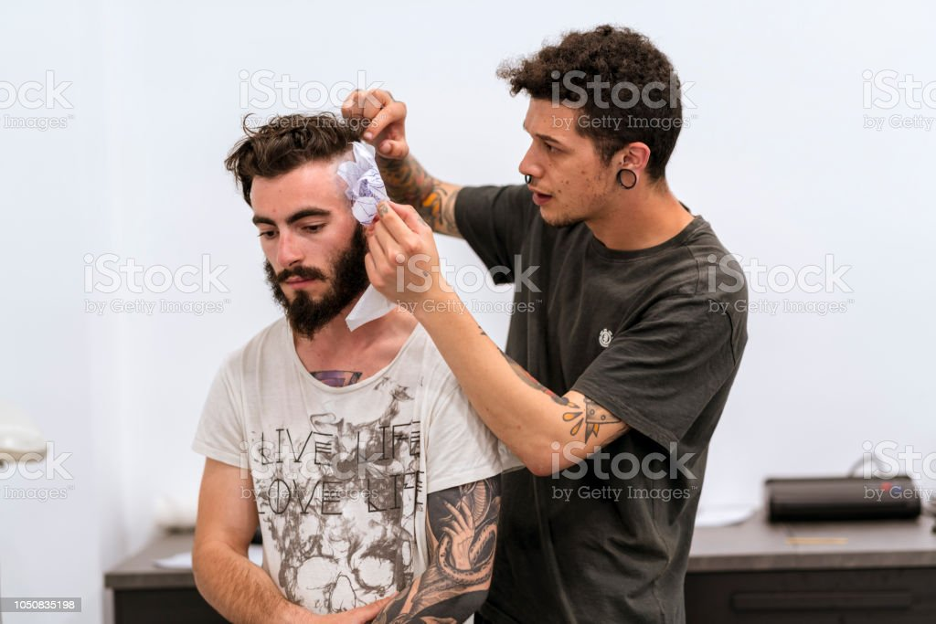 Tattooist placing the drawing on the head. стоковое фото