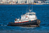Old tug in Seattle harbot with blue water and a few whitecaps.