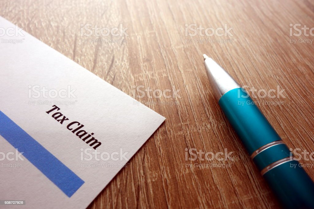 Tax claim form and pen on desk stock photo