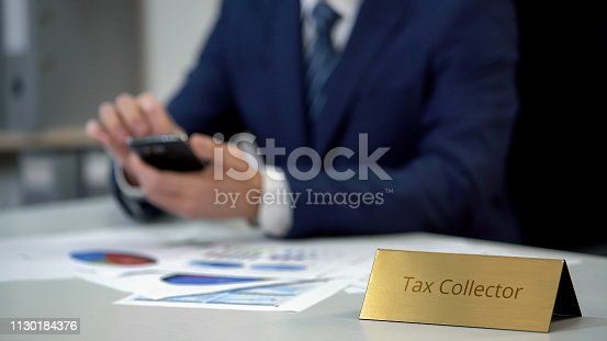 istock Tax collector using smartphone at work, checking debt statistics in diagrams 1130184376