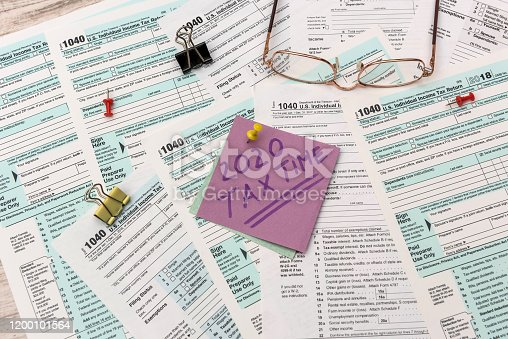 1185240988 istock photo 2020 Tax Company. Colorful stickers with reminder at 1040 tax form close up 1200101564