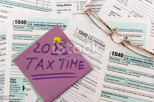 1185240988 istock photo 2020 Tax Company. Colorful stickers with reminder at 1040 tax form close up 1200680609