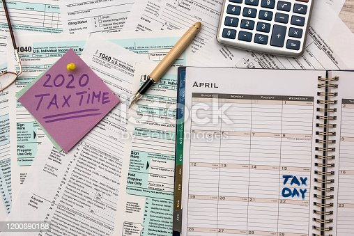 1185240988 istock photo 2020 Tax Company. Colorful stickers with reminder at 1040 tax form close up 1200690188