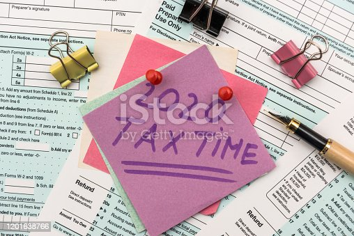 1185240988 istock photo 2020 Tax Company. Colorful stickers with reminder at 1040 tax form close up 1201638766