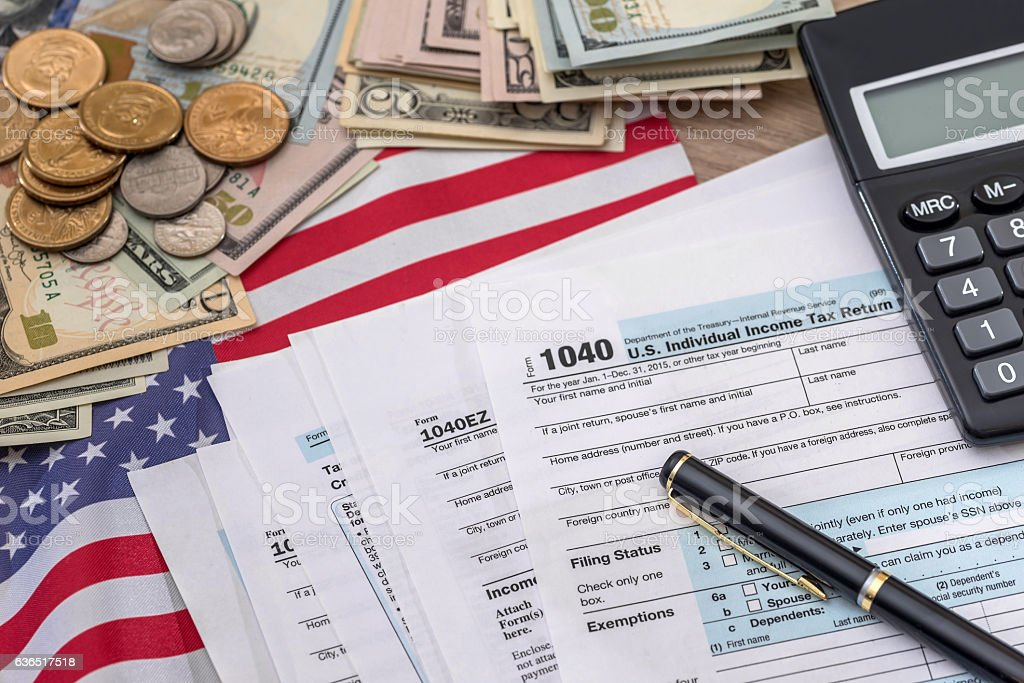 tax concept - 1040 tax form, pen, us money and stock photo