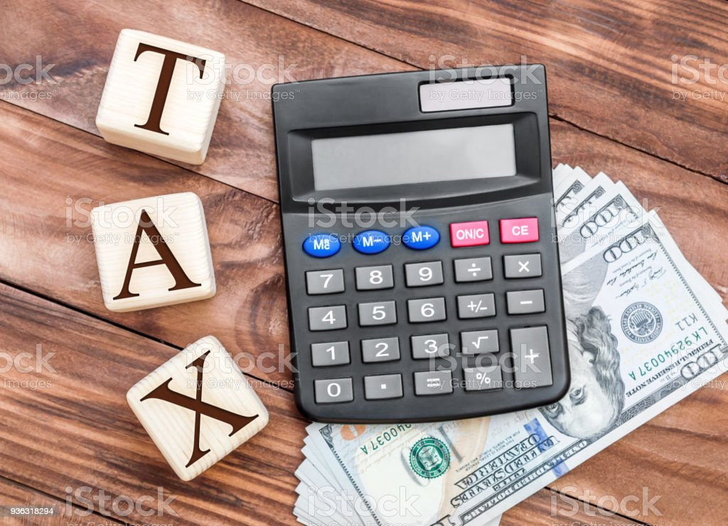 Tax concept. Calculator, money and wooden cubes with word TAX on the table. Top view. stock photo