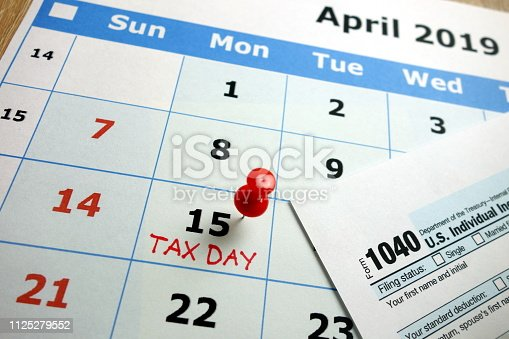 Tax day marked on April 2019 monthly calendar with 1040 form