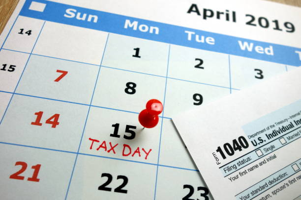 Tax day 2019 Tax day marked on April 2019 monthly calendar with 1040 form taxes stock pictures, royalty-free photos & images