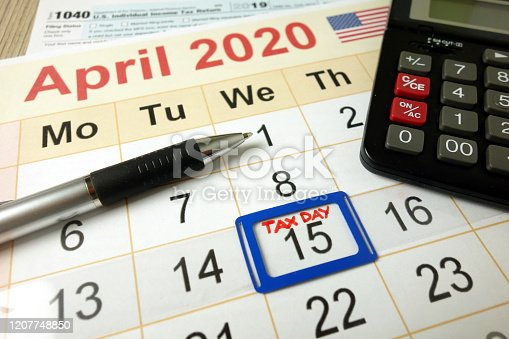 1170746979 istock photo Tax day marked on April 2020 monthly calendar with 1040 form calculator and pen 1207748850