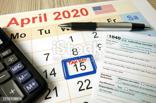 1170746979 istock photo Tax day marked on April 2020 monthly calendar with 1040 form pen and calculator 1210128974