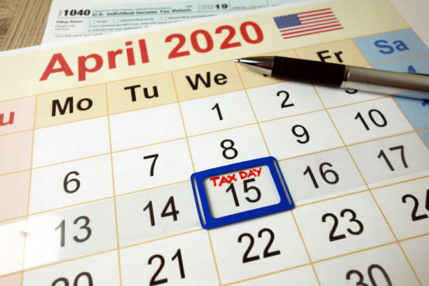 Tax day marked on April 2020 monthly calendar with 1040 form stock photo