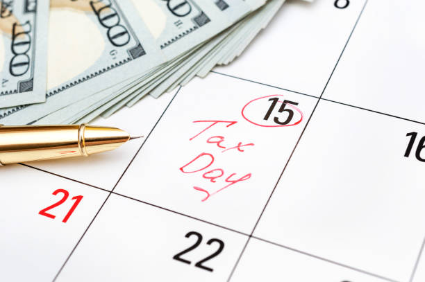 Tax day written on calendar and money. Close up. stock photo