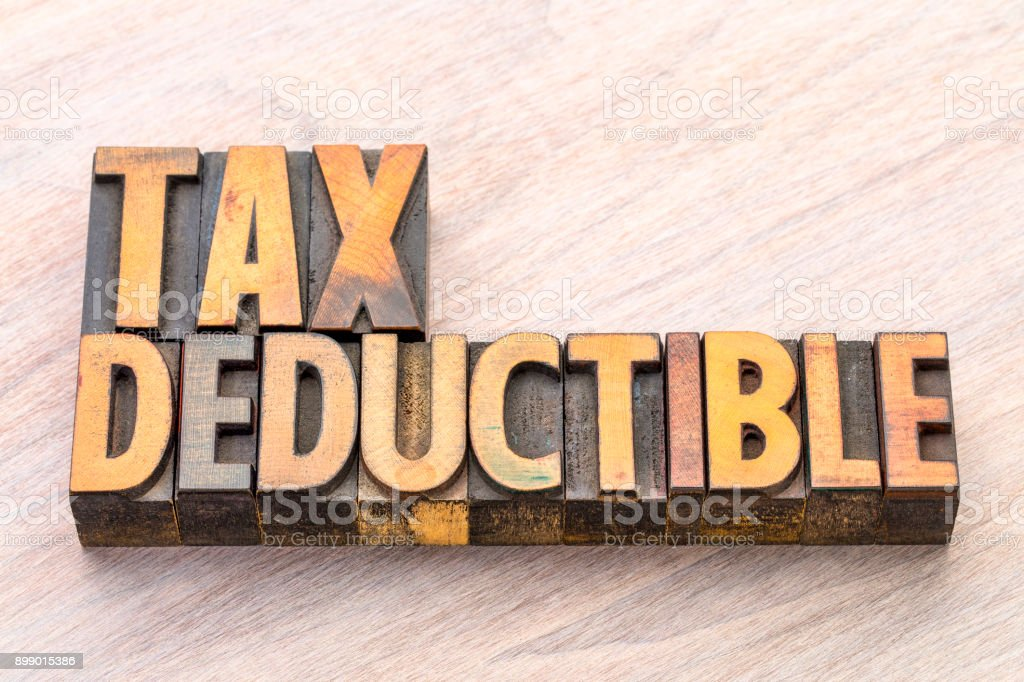 tax deductible word abstract in wood type stock photo
