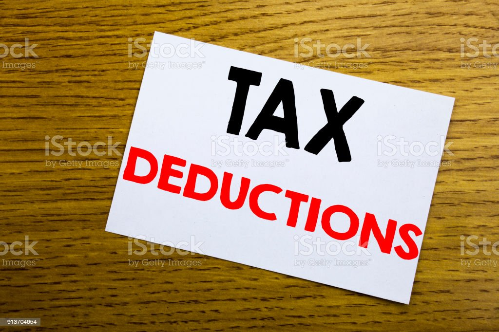 Tax Deductions. Business concept for Finance Incoming Tax Money Deduction written on sticky note, wooden wood background with copy space. stock photo