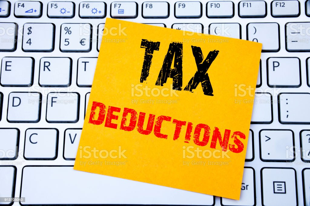 Tax Deductions. Business concept for Finance Incoming Tax Money Deduction written on sticky note paper on the white keyboard background. stock photo