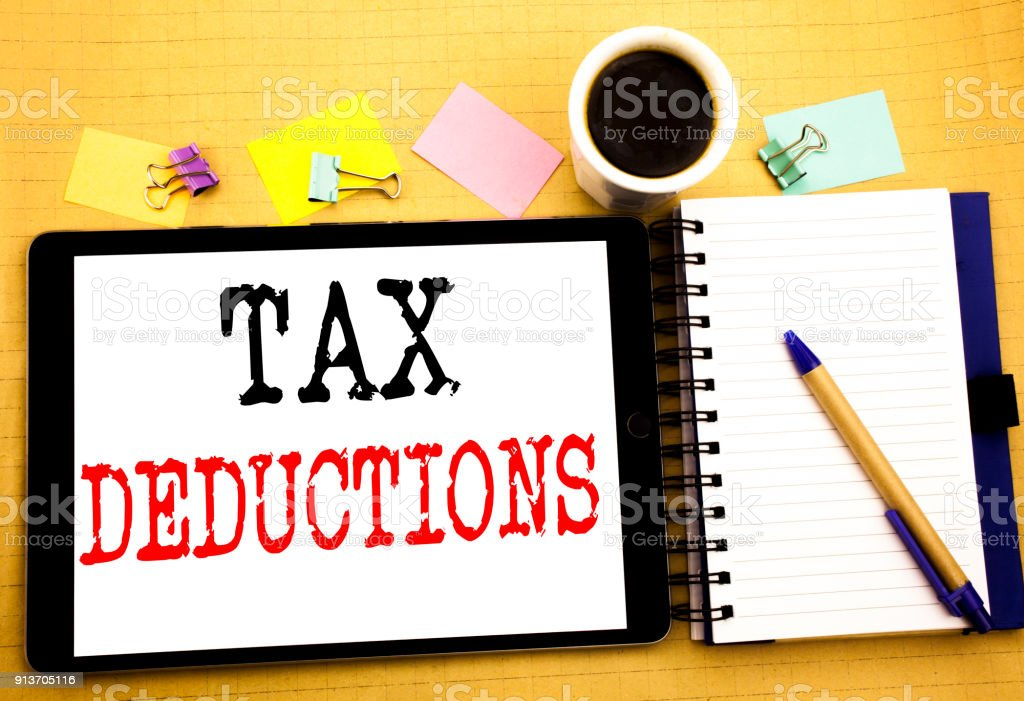 Tax Deductions. Business concept for Finance Incoming Tax Money Deduction Written on tablet laptop, wooden background with sticky note, coffee and pen stock photo