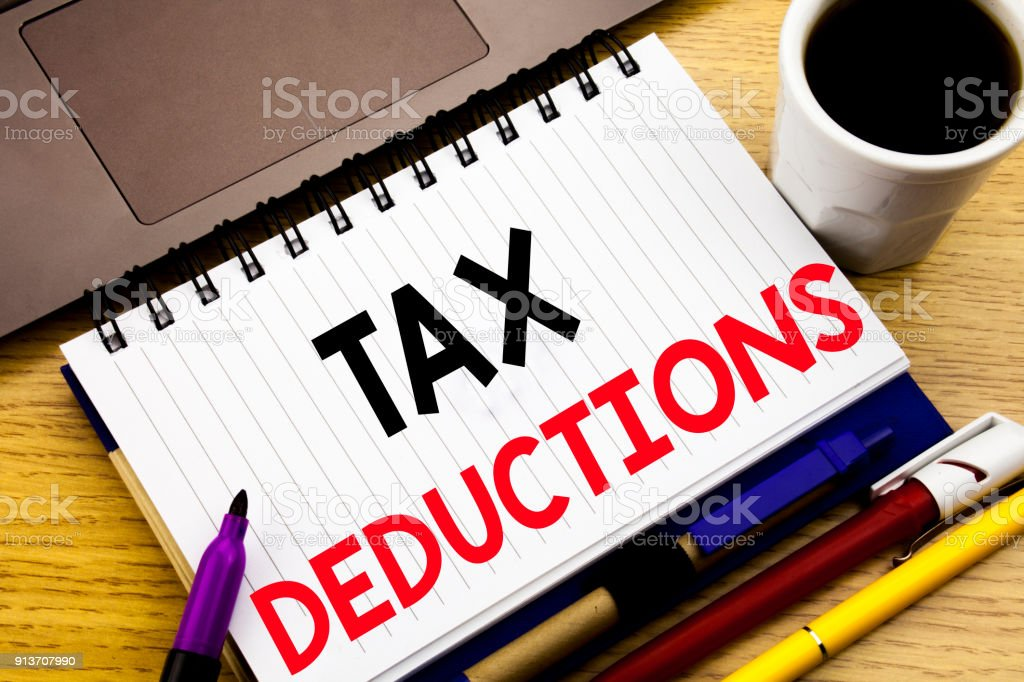 Tax Deductions. Business concept for Finance Incoming Tax Money Deduction written on notebook book on the wooden background in the Office with laptop coffee stock photo