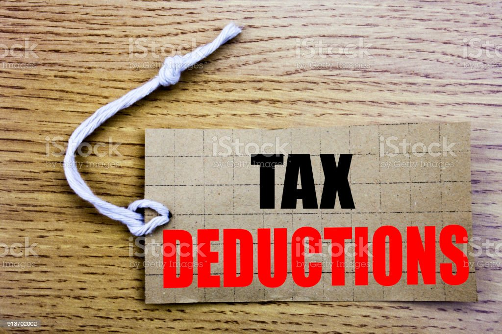 Tax Deductions. Business concept for online saleFinance Incoming Tax Money Deduction written on price tag paper with copy space on the wooden vintage background stock photo