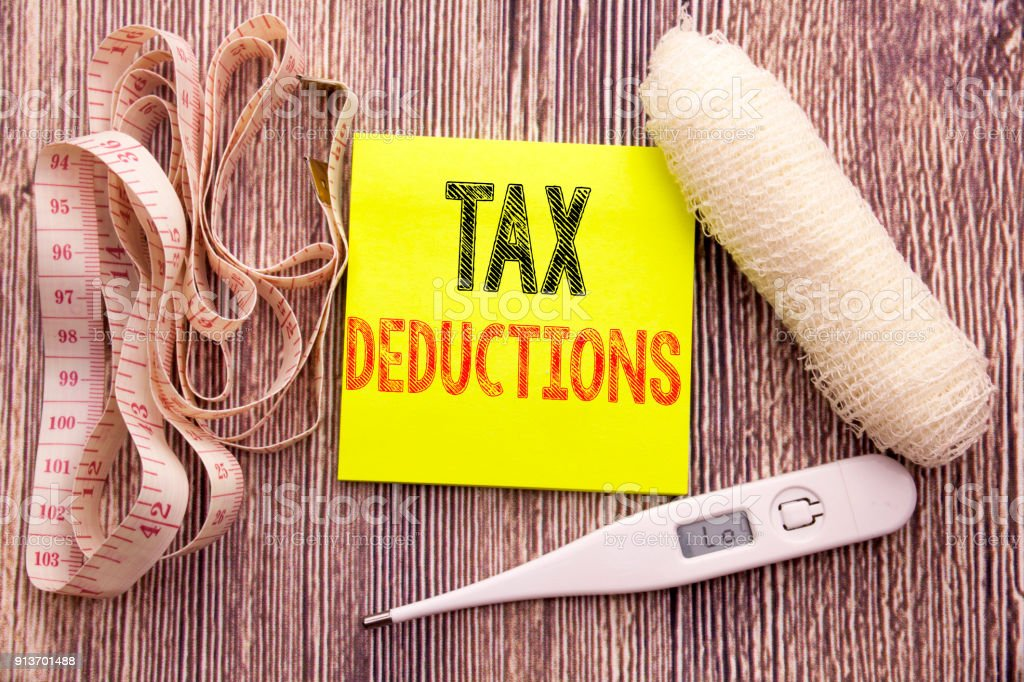 Tax Deductions. Business fitness health concept for Finance Incoming Tax Money Deduction written sticky note empty paper background with copy space bandage and thermometer stock photo