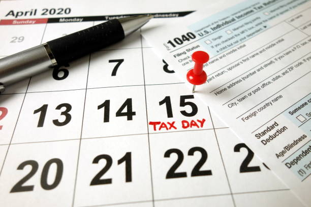 USA tax due date marked on calendar - 15 April 2020, blank 1040 form and pen stock photo