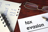 istock Tax evasion written on a paper. 615422762