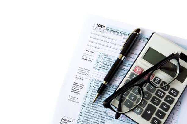 U.S Tax Filing Top view of calculator, pen, eyeglasses and out of focus U.S IRS 1040 form income tax stock pictures, royalty-free photos & images