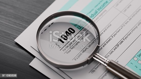 1040 US tax form and a magnifying glass on black wood surface. Horizontal composition with selective focus and copy space.