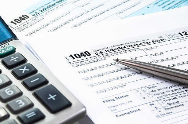 tax form tax form 1040 with calculator in blue tone and desaturated colors economic reform stock pictures, royalty-free photos & images