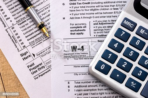 istock tax form w 4 with calculator and pen 899346596