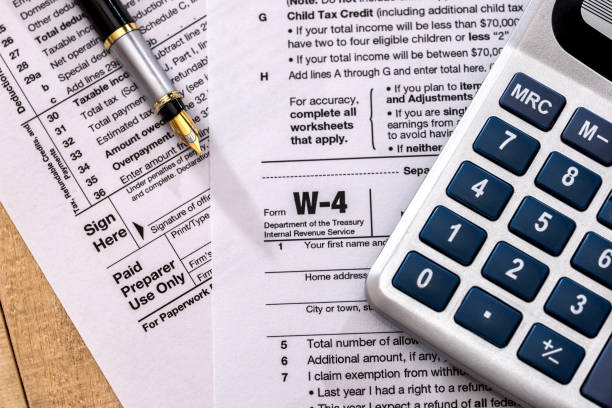 tax form w 4 with calculator and pen tax form w 4 with calculator and pen letter w stock pictures, royalty-free photos & images