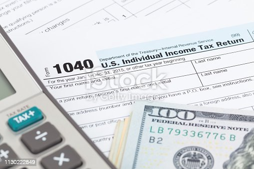 1145921132istockphoto Tax form with calculator and dollar banknote 1130222849