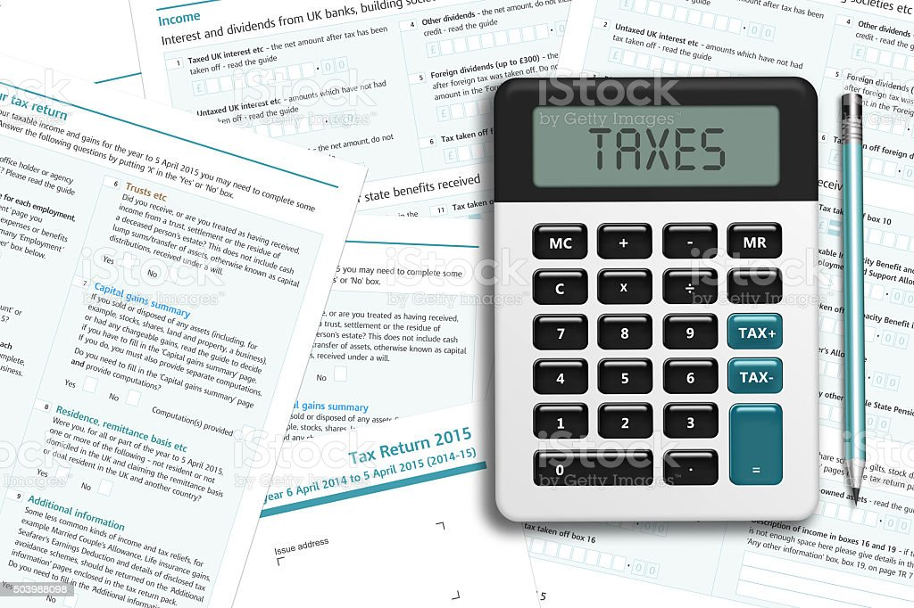 UK tax form with calculator lying on wooden desk stock photo