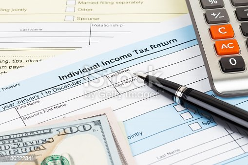 1145921132istockphoto Tax form with calculator, pen, and dollar banknote; document are mock-up 1130222841