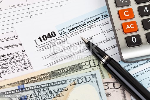 istock Tax form with calculator, pen, and dollar banknote 1130222764