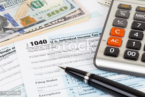 istock Tax form with calculator, pen, and dollar banknote 1130222785