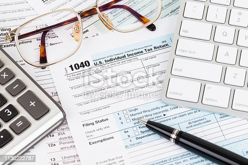istock Tax form with calculator, pen, glasses, and keyboard 1130222787