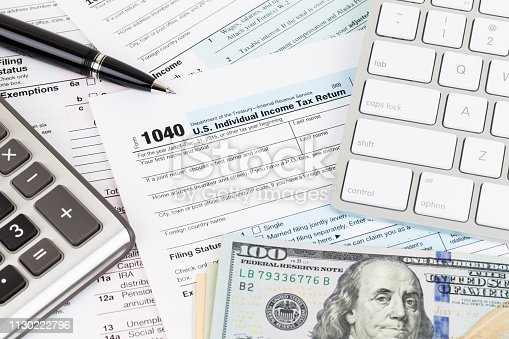 istock Tax form with calculator, pen, keyboard, and dollar banknote 1130222796
