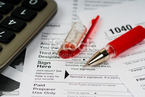 istock 1040 tax form with focus on sign here text and red pen 896229098