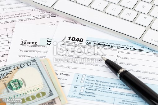 1145921132istockphoto Tax form with keyboard, pen, and dollar banknote 1130222779