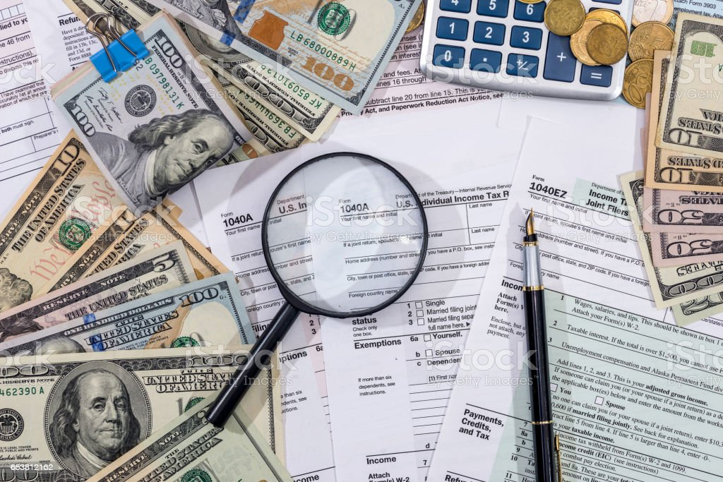 1040 Tax Form with magnifying glass dollars, pen and calculator. stock photo
