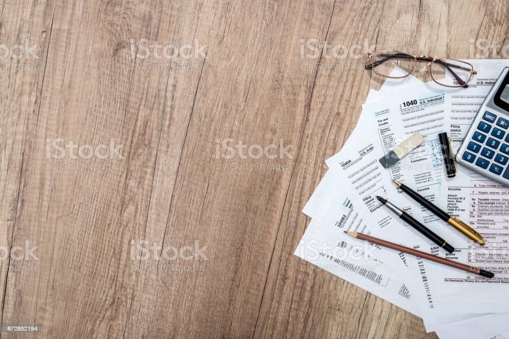 tax form with notepad, pen, pencil and calculator stock photo