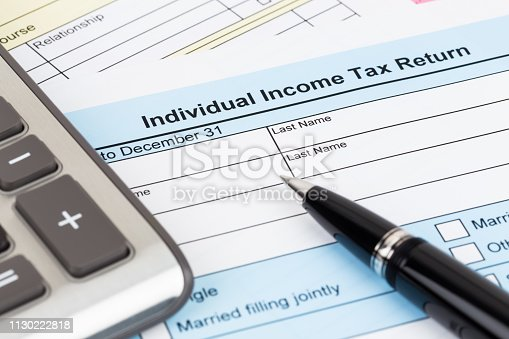 istock Tax form with pen and calculator; document are mock-up 1130222818