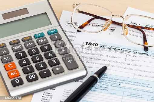 1145921132istockphoto Tax form with pen, glasses, and calculator 1130222775