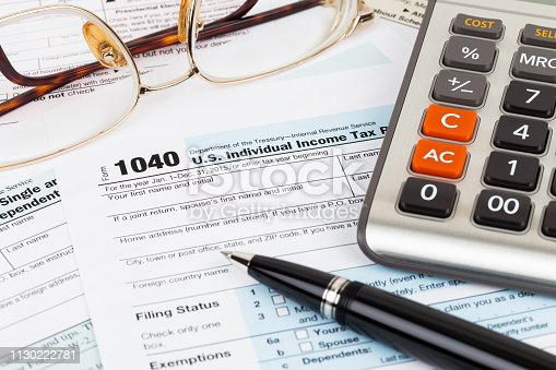 istock Tax form with pen, glasses, and calculator 1130222781