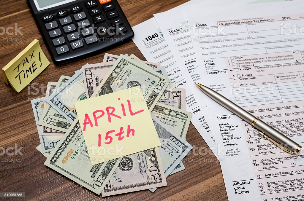 1040 tax form with stick april 15,  dollar  and calculator stock photo